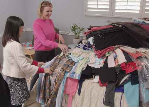 Marie-Kondo-with-pile-of-clothes-on-bed